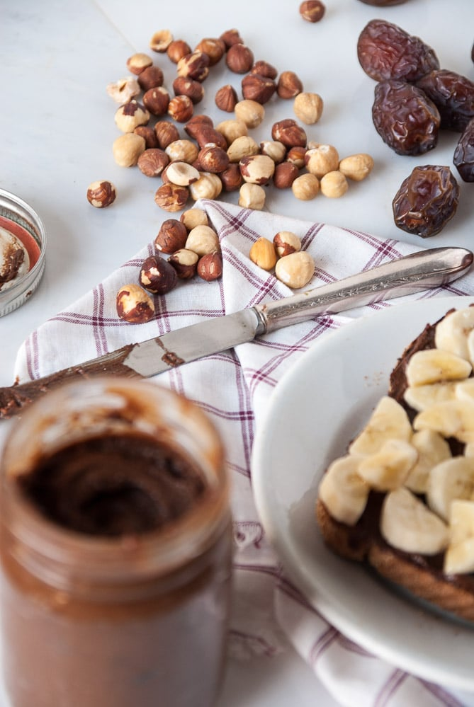 Homemade Vegan Nutella next to dates and hazelnuts