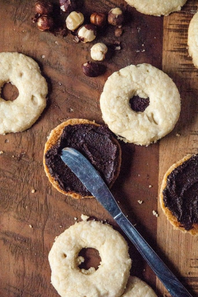 Vegan Linzer Cookies with Nutella - Vegan linzer cookies get a chocolate twist with a homemade nutella filling, perfect for holiday baking!