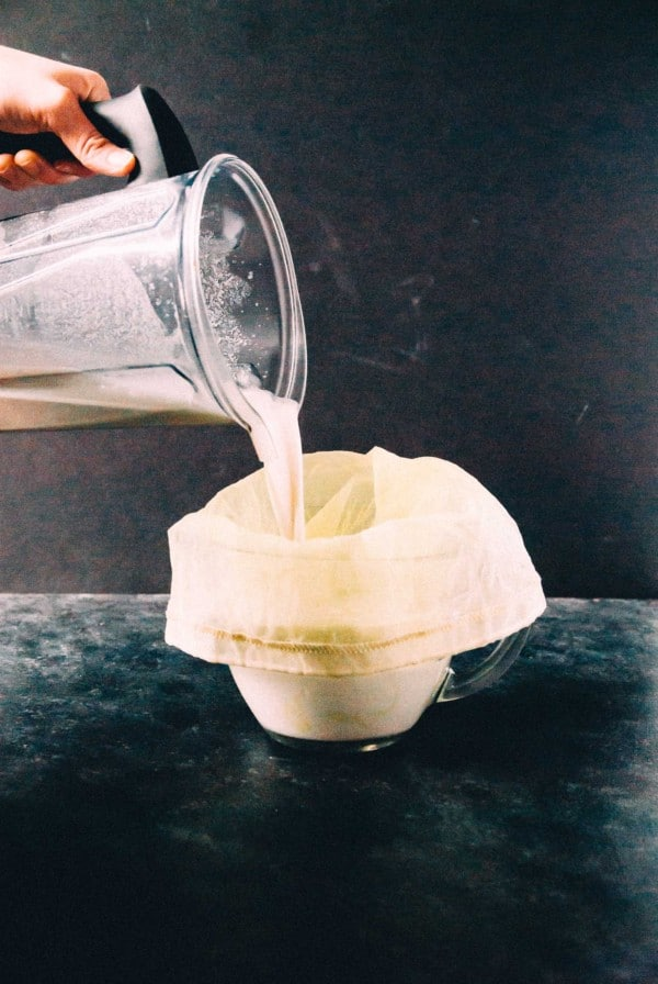 pouring homemade cashew milk into a nut milk bag