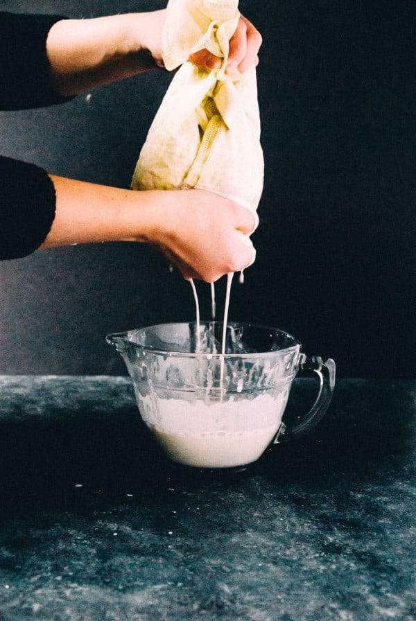straining homemade cashew milk in a nut milk bag