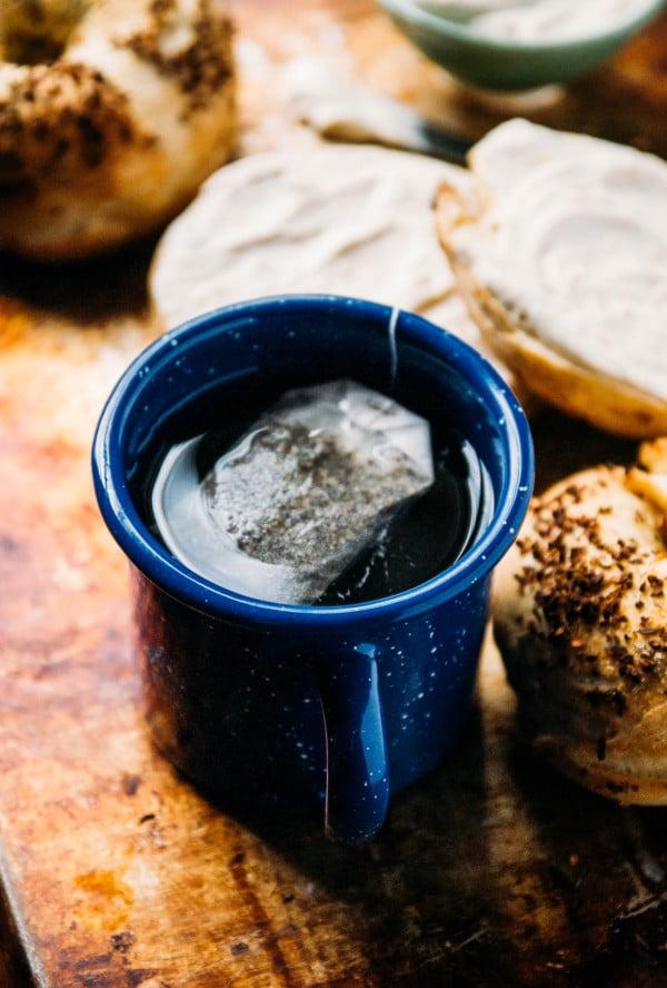 mug of tea next to an herb and onion bagel