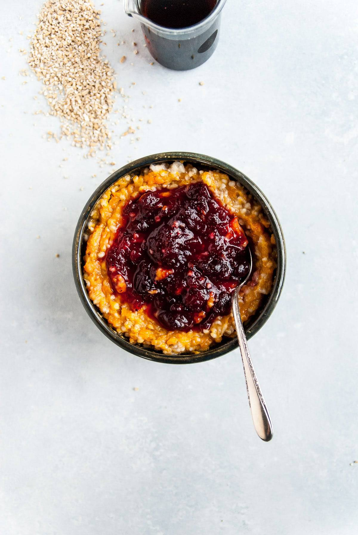 The perfect way to use up Thanksgiving leftovers, this vegan sweet potato oatmeal is topped with cranberry sauce and perfect for prepping ahead!
