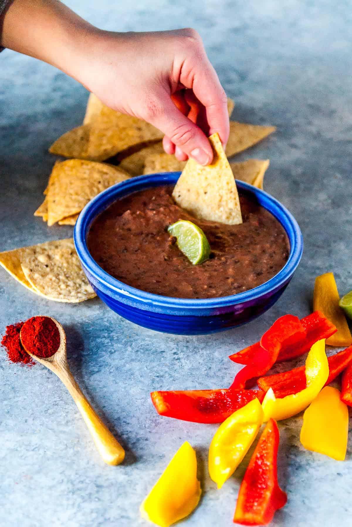 dipping a tortilla chip into vegan black bean dip