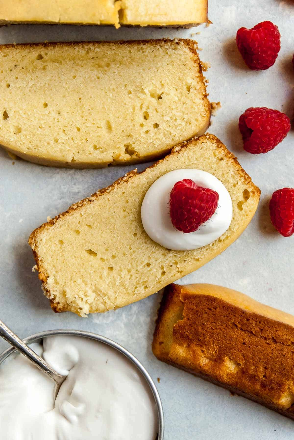 slices of vegan pound cake with raspberries and coconut whipped cream on a spoon