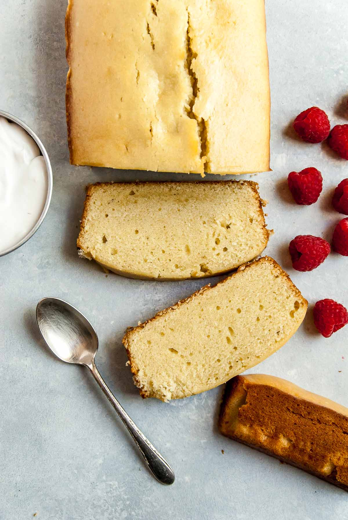 Slices of vegan pound cake with raspberries on blue background
