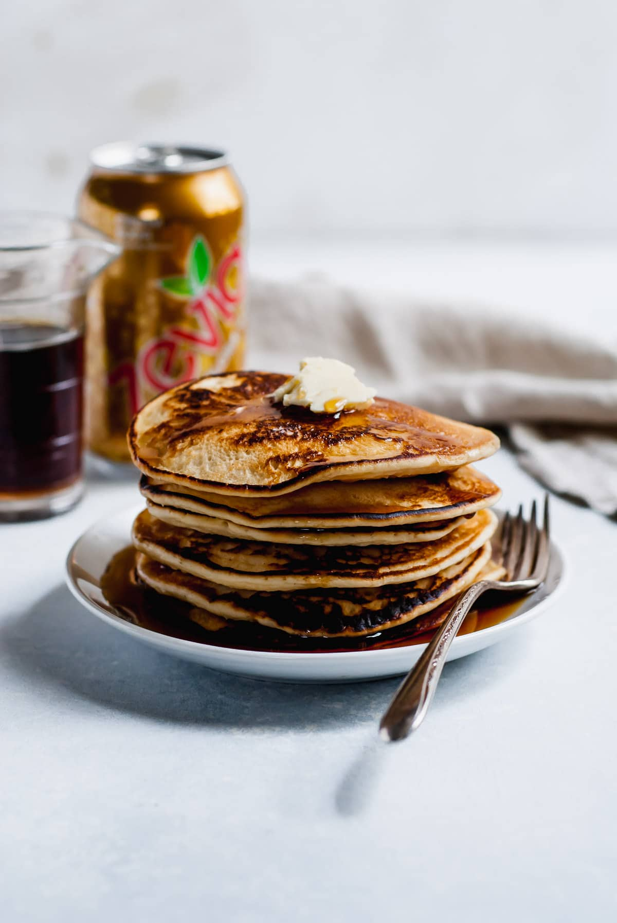 pancakes on a plate with a fork and can of soda