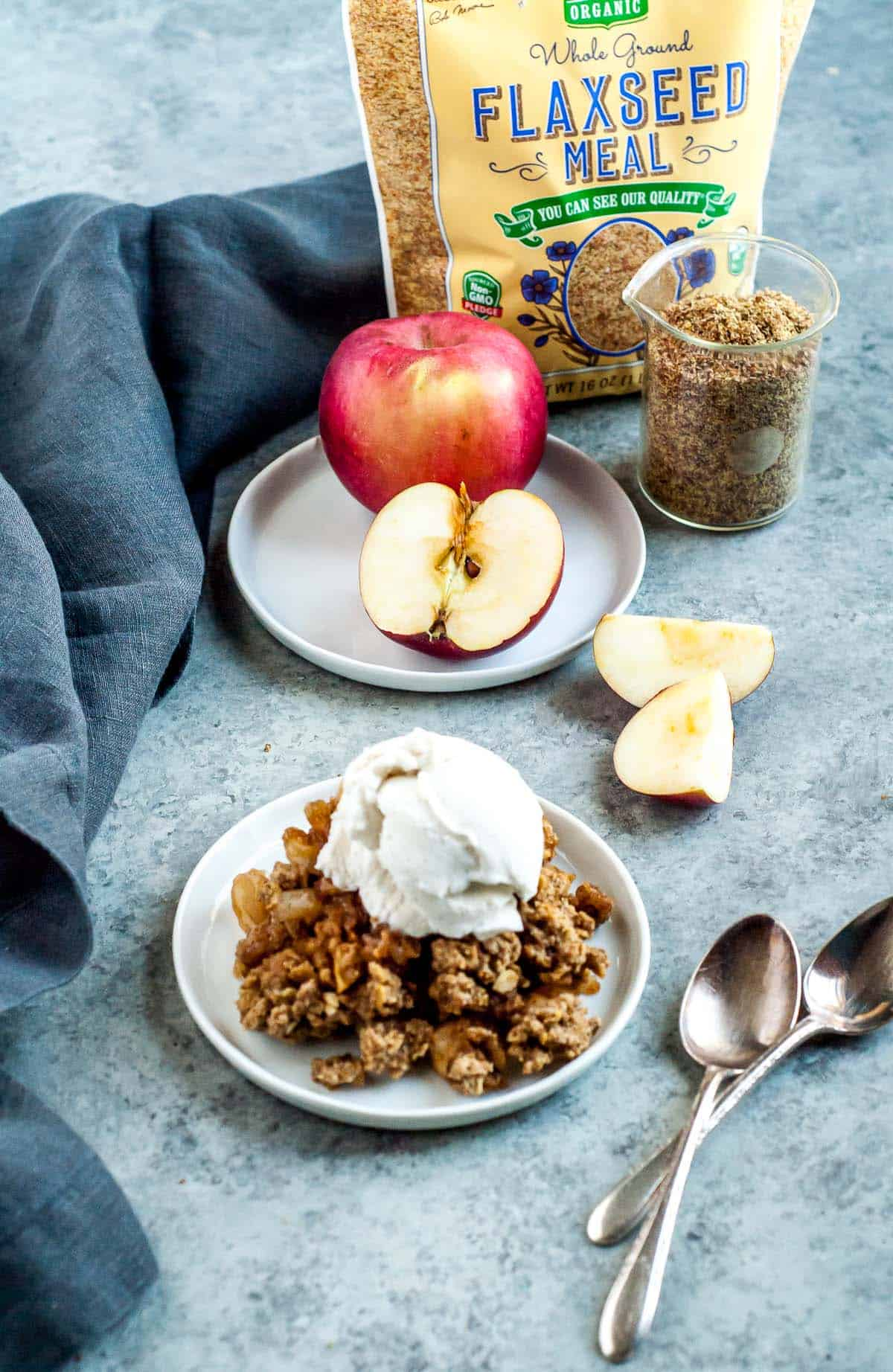 apple crisp on a white plate with apple in the background