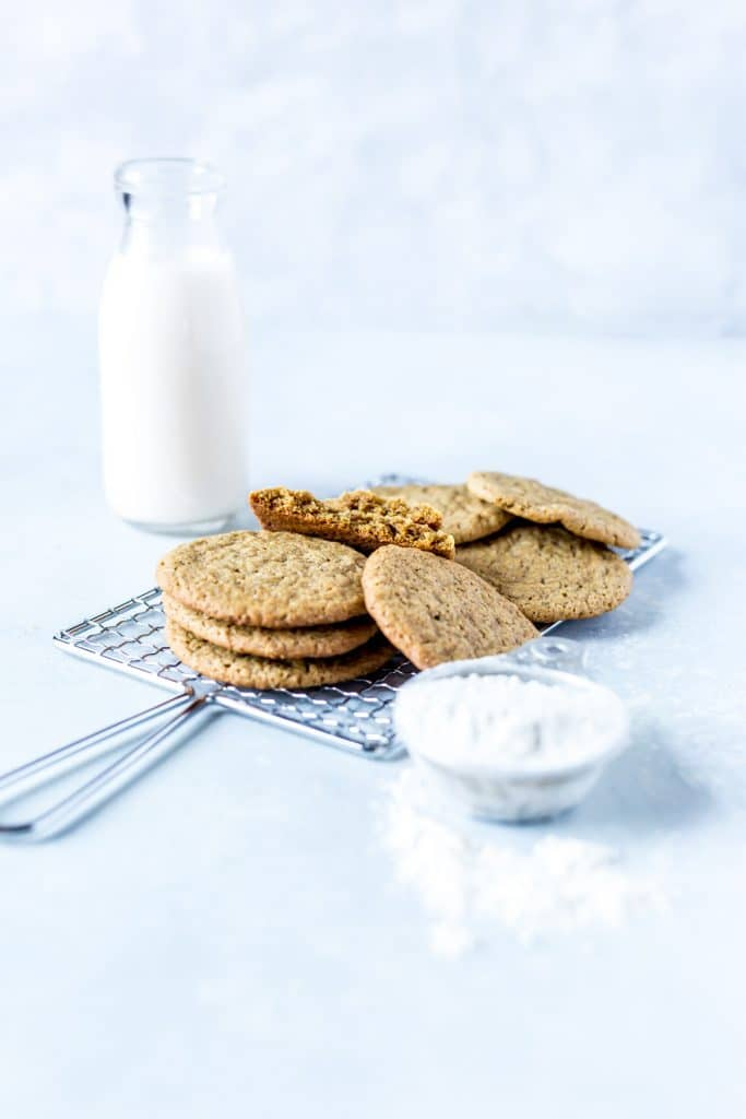 stack of ginger cookies with cup of milk and cup of flour