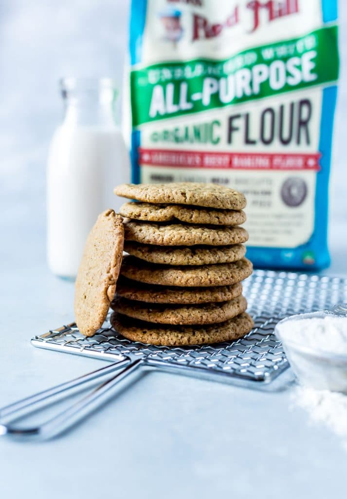 stack of ginger cookies on silver rack with cup of flour and glass of milk