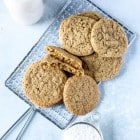 vegan ginger cookies on a silver rack with a glass of milk and cup of flour on blue background