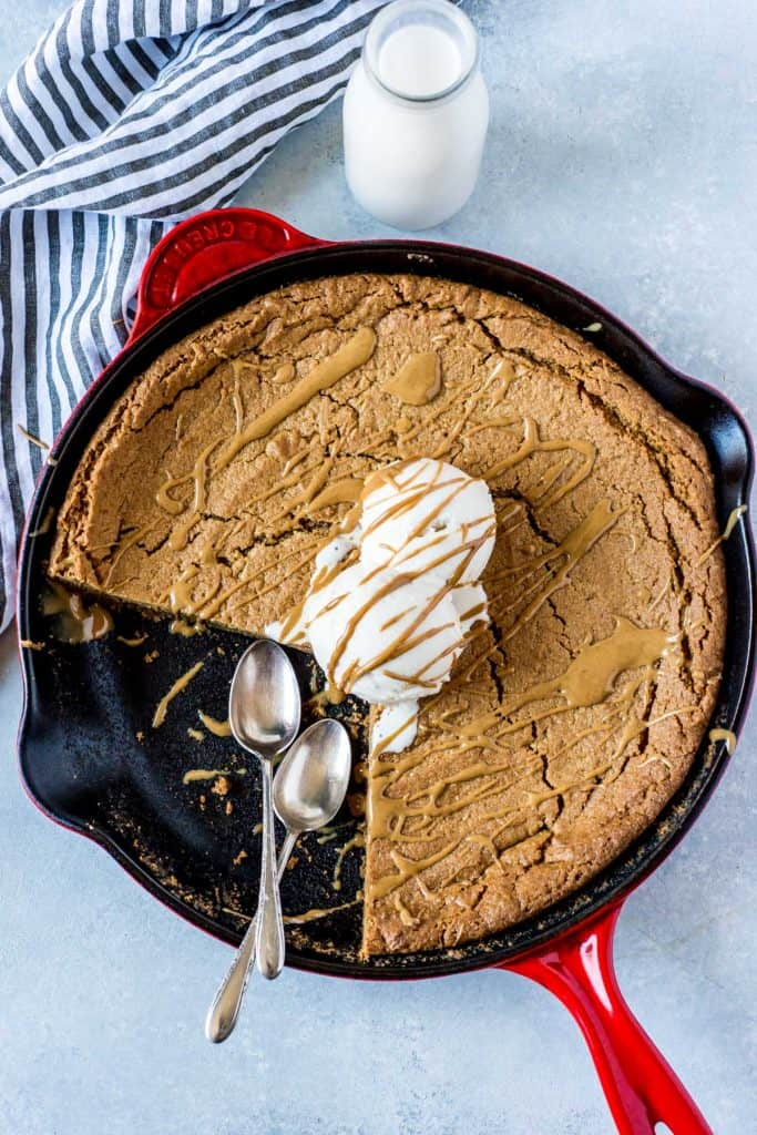 Deep dish peanut butter skillet cookie with scoops of ice cream on top with two spoons.