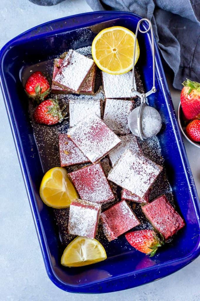 Tray of strawberry lemon bars in a blue pan with strawberries and lemon wedges