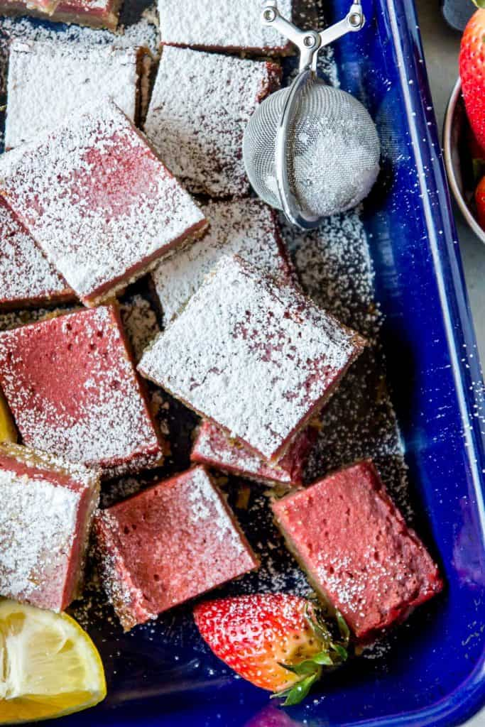 Strawberry lemon bars in a blue pan with a close up on a bar