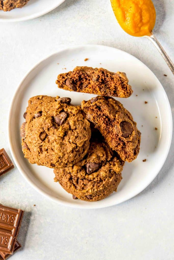 Plate of chocolate pumpkin cookies on white background