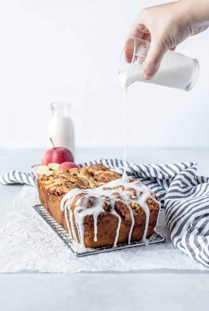 loaf of apple cinnamon babka with glaze being poured over it