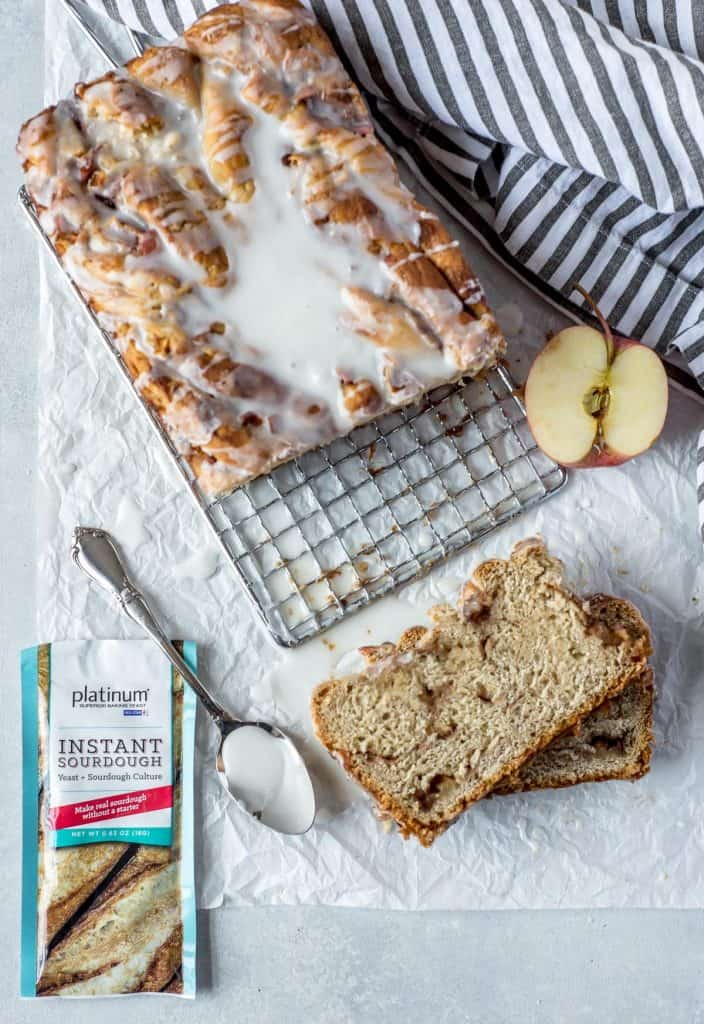 loaf of babka with yeast pack and spoon with glaze on white background